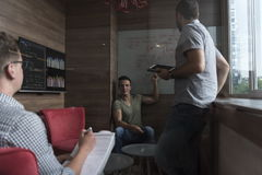 Team meeting and brainstorming in small private office. Young people group in small private office have team meeting and brainstorming while working on laptop Stock Photos