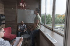 Team meeting and brainstorming in small private office. Young people group in small private office have team meeting and brainstorming while working on laptop Stock Photo