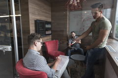 Team meeting and brainstorming in small private office. Young people group in small private office have team meeting and brainstorming while working on laptop Royalty Free Stock Image