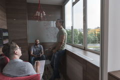 Team meeting and brainstorming in small private office. Young people group in small private office have team meeting and brainstorming while working on laptop Royalty Free Stock Photo