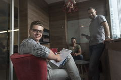 Team meeting and brainstorming in small private office. Young people group in small private office have team meeting and brainstorming while working on laptop Stock Images