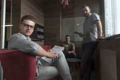Team meeting and brainstorming in small private office. Young people group in small private office have team meeting and brainstorming while working on laptop Royalty Free Stock Photos
