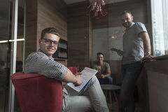 Team meeting and brainstorming in small private office. Young people group in small private office have team meeting and brainstorming while working on laptop Stock Photography