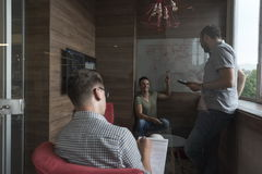 Team meeting and brainstorming in small private office. Young people group in small private office have team meeting and brainstorming while working on laptop Royalty Free Stock Images