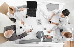 Team meeting from overhead view. Businesspeople discussing work at office meeting table royalty free stock photography