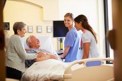 Team Meeting With Senior Couple médico en sitio de hospital imágenes de archivo libres de regalías