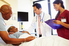 Team Meeting With Senior Couple medico nella stanza di ospedale Immagini Stock