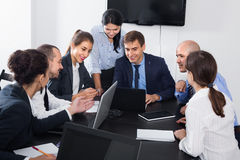 Team member explaining issue on project to coworkers Stock Photo