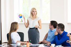 Team members listening attentively to a business woman holding a Stock Photo
