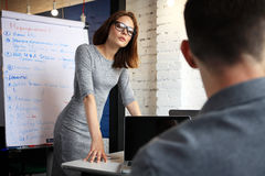 Team members listening attentively to a cheerful business woman holding a presentation. Royalty Free Stock Image