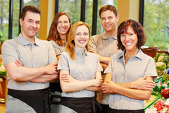 Team of men and women staff. Happy team of smiling men and women staff in a supermarket Royalty Free Stock Image