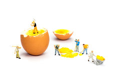 Team of miniature human figurines transporting chicken egg yolk. Team of miniature  construction workers figurines transporting chicken egg yolk Stock Photo