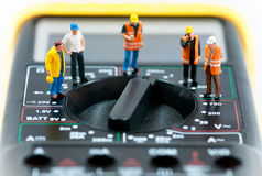 Team of miniature workers on top of multimeter. Macro photo Stock Photos