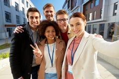 Team mit den Konferenzausweisen, die selfie in der Stadt nehmen Lizenzfreies Stockbild