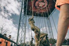 Team a mulher de ajuda à corda de escalada em um teste da raça de obstáculo Foto de Stock