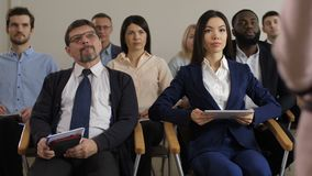 Team of multi ethnic business people at seminar. Diverse business colleagues attentively listening speech of professional public speaker during seminar. Audience stock video footage
