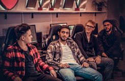 A team of multiracial teenage gamers sitting on gamer chairs and looking at a camera in a gaming club or internet cafe. royalty free stock images