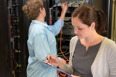 Team of network technician in datacenter. Checking security on servers stock photography
