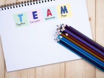 TEAM on notebook 2. Word spelling TEAM and handwriting together, everyone, achieve, more on notebook with wood background (Business Concept Royalty Free Stock Photos