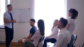 Team o treinamento, o plano de negócios novo dos presentes do orador no whiteboard e na moça feliz faz perguntas no seminário video estoque