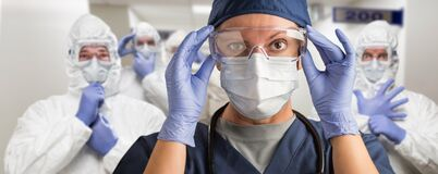 Free Team Of Female And Male Doctors Or Nurses Wearing Personal Protective Equipment In Hospital Hallway Royalty Free Stock Image - 177399566