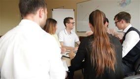Team Of Office Employees Discussing en un proyecto creativo en la sala de reunión Un grupo de miembros jovenes del funcionamiento almacen de video