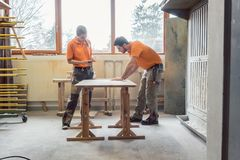 Team oft wo carpenters working on a table. Polishing and varnishing royalty free stock photography