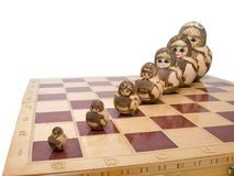 Team ordered of nested dolls. Row ordered nested dolls on the chessboard isolated. Team work concept Royalty Free Stock Photo