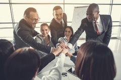Cheerful colleagues giving high fives. We are team. Outgoing partners demonstrating unity while situating at desk. Achievement in labor concept Stock Photography