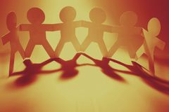 Paper chain team holding hands. Team of paper chain people in a row holding hands Royalty Free Stock Photography