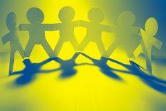 Paper chain team holding hands. Team of paper chain people in a row holding hands Stock Photo