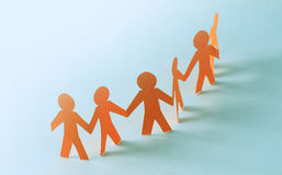 Team of paper doll people holding hands Stock Photography