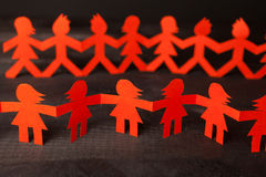 Team of paper doll people holding hands Royalty Free Stock Photography
