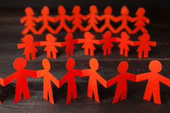 Team of paper doll people holding hands Stock Photos