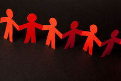 Team of paper doll people holding hands Royalty Free Stock Images