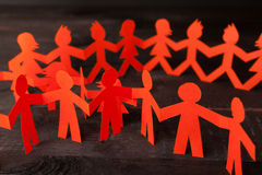 Team of paper doll people holding hands Royalty Free Stock Image