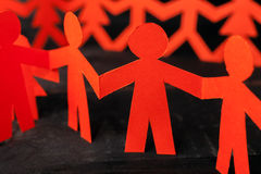 Team of paper doll people holding hands royalty free stock photos