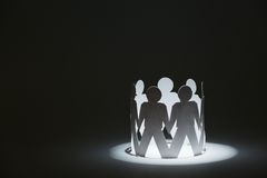 Team of paper doll people holding hands in light Stock Photography