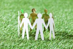 Team of paper people on grassy field Royalty Free Stock Photography