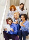 Team with papers and take away coffee on staircase Royalty Free Stock Photo