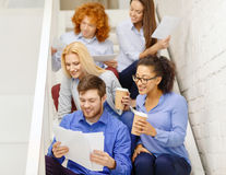 Team with papers and take away coffee on staircase Stock Image