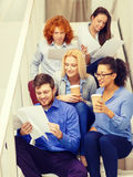 Team with papers and take away coffee on staircase Royalty Free Stock Image