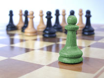 Team of pawns with green leader. Metaphor of a business team with leader in the front royalty free stock image