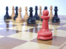 Team of pawns with red leader. Metaphor of a business team with red leader Royalty Free Stock Photos