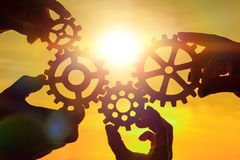 Team of people with gears in hands on sunset background. Business. interaction stock photo
