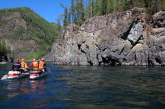 Team of people on an inflatable catamaran raft on a river canyon. Royalty Free Stock Photography