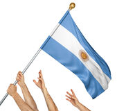Team of peoples hands raising the Argentina national flag Royalty Free Stock Photo