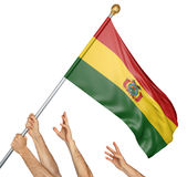 Team of peoples hands raising the Bolivia national flag. 3D rendering isolated on white background Royalty Free Stock Photos