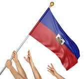 Team of peoples hands raising the Haiti national flag. 3D rendering isolated on white background royalty free stock images