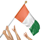 Team of peoples hands raising the Ivory Coast national flag stock images